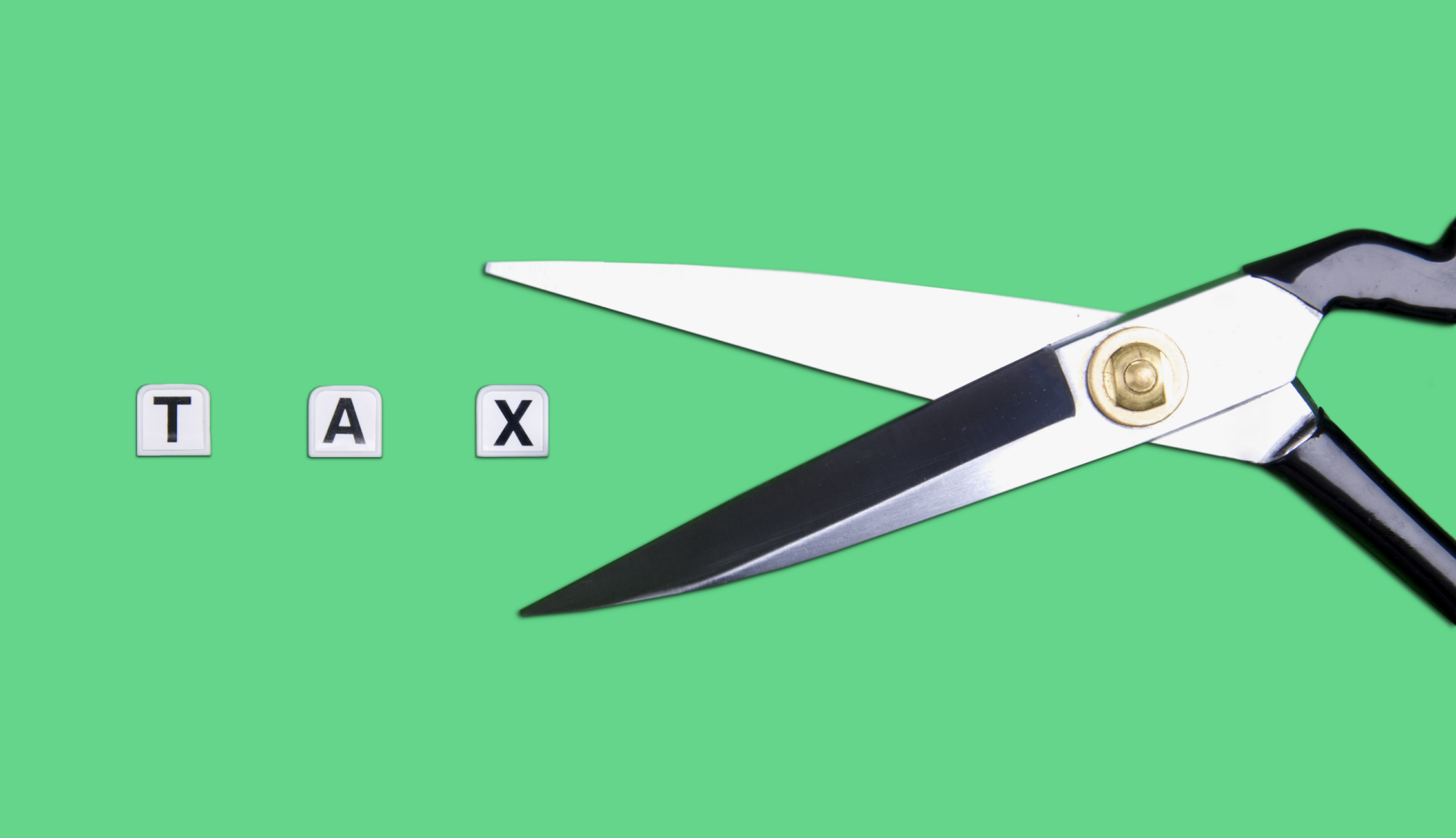 Scissors and TAX on a green background.