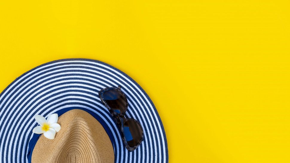 Sun hat and sunglasses on a yellow background.