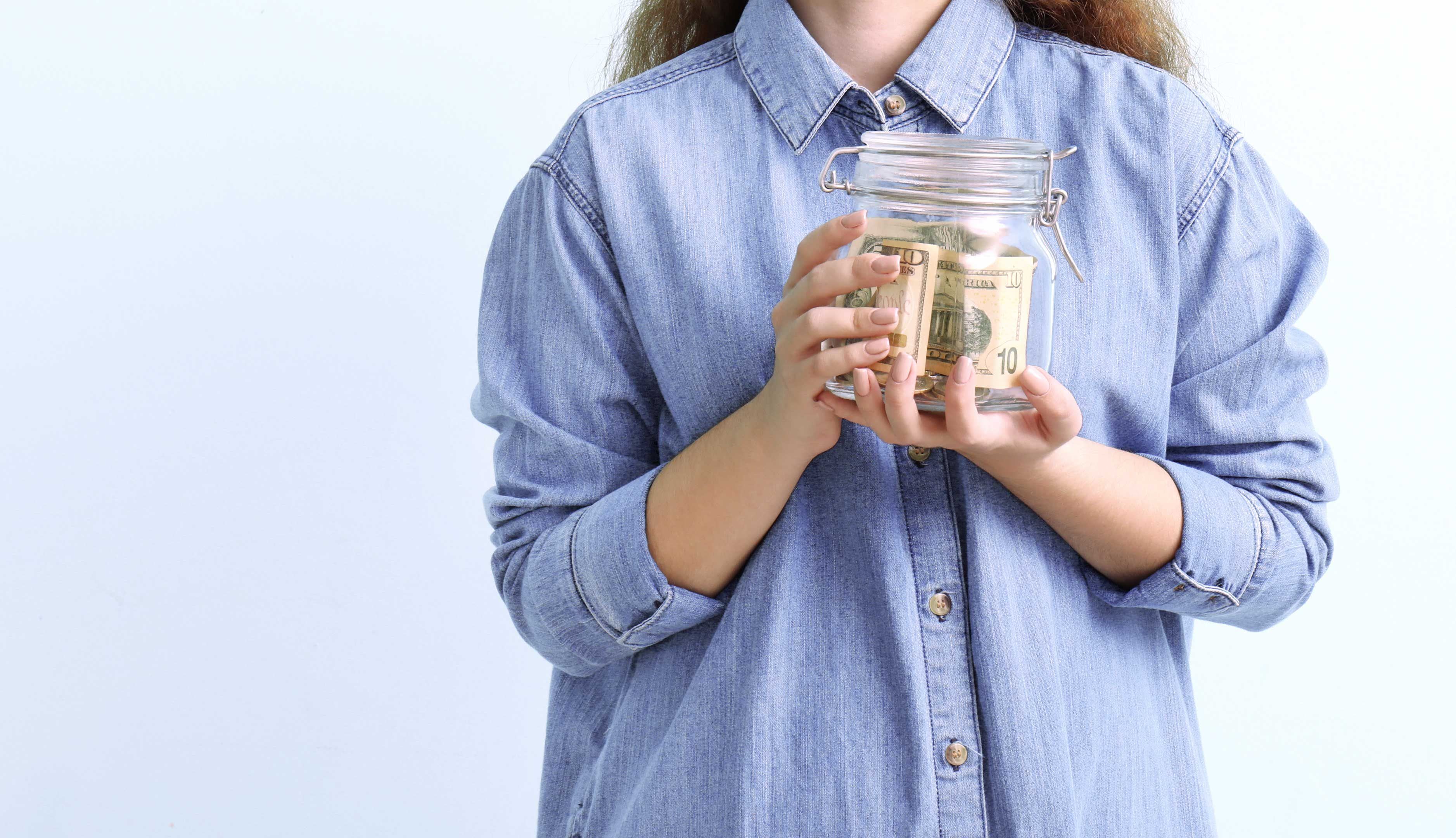 Girl holding spare change in a jar.