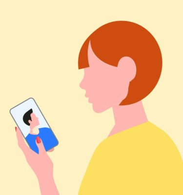 girl on yellow background looking at phone