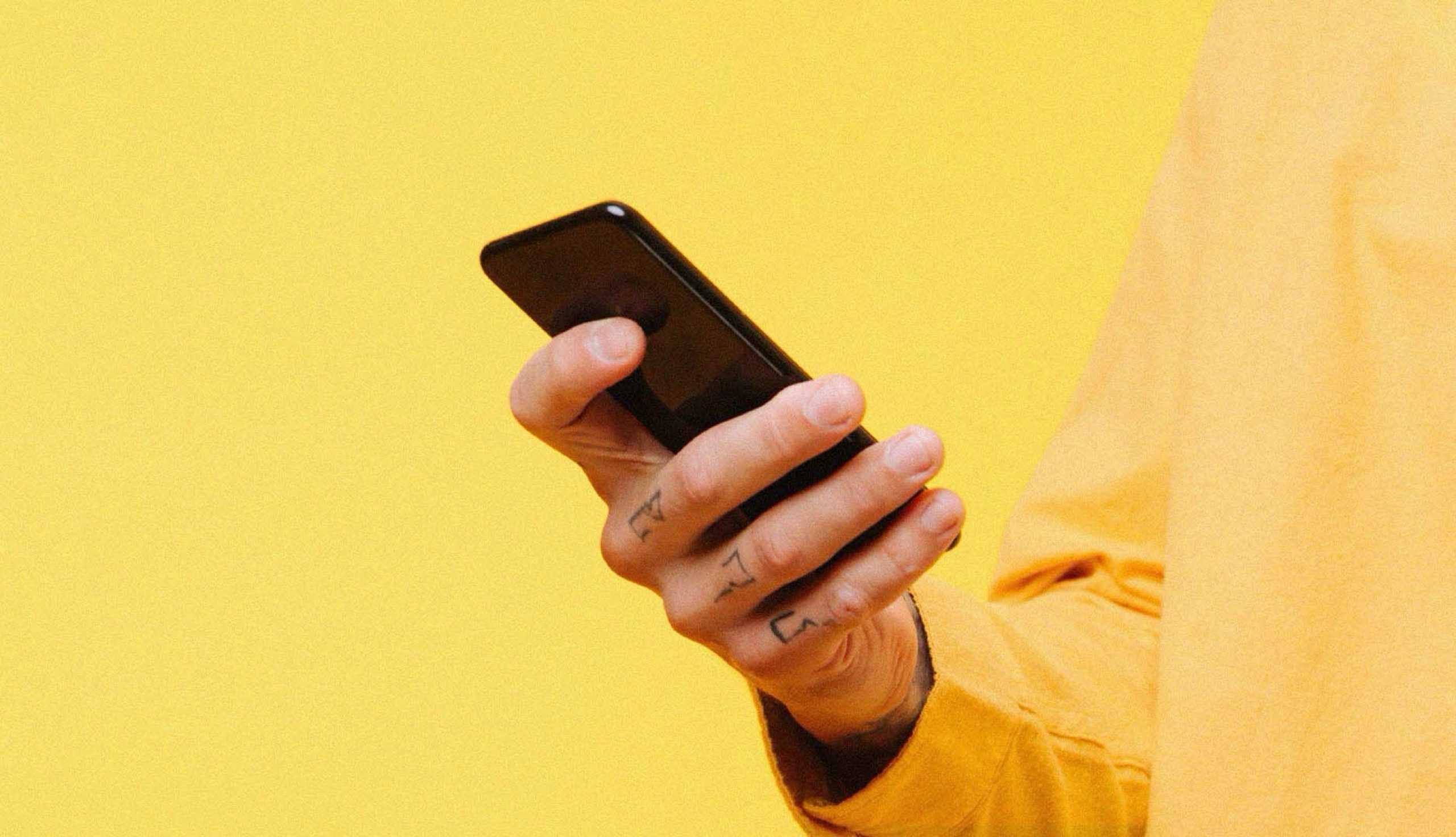 man's hand holding a phone on yellow background